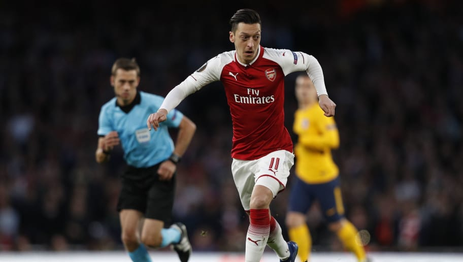 Arsenal's German midfielder Mesut Ozil runs with the ball during the UEFA Europa League first leg semi-final football match  between Arsenal and Atletico Madrid at the Emirates Stadium in London on April 26, 2018. (Photo by Adrian DENNIS / AFP)        (Photo credit should read ADRIAN DENNIS/AFP/Getty Images)