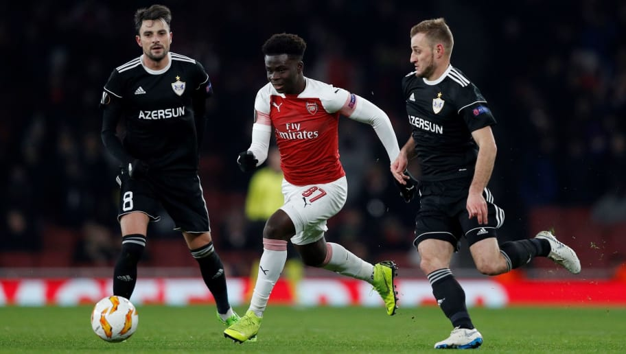 Arsenal's English striker Bukayo Saka (C) vies with Qarabag's Azerbaijan defender Maksim Medvedev (R) during their UEFA Europa league Group E football match between Arsenal and FK Qarabag at the Emirates stadium in London on December 13, 2018. (Photo by Adrian DENNIS / AFP)        (Photo credit should read ADRIAN DENNIS/AFP/Getty Images)