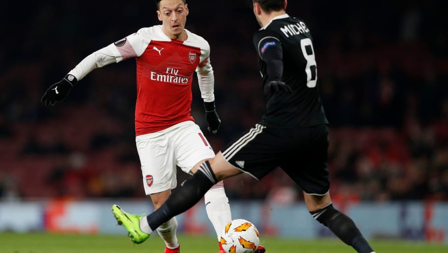 Arsenal's German midfielder Mesut Ozil (L) vies with Qarabag's Spanish midfielder Michel during their UEFA Europa league Group E football match between Arsenal and FK Qarabag at the Emirates stadium in London on December 13, 2018. (Photo by Adrian DENNIS / AFP)        (Photo credit should read ADRIAN DENNIS/AFP/Getty Images)