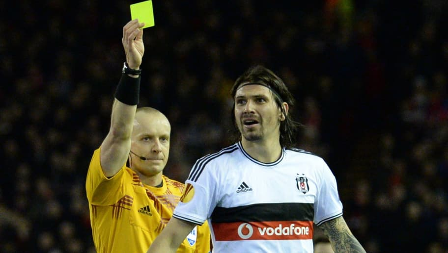 Besiktas' Turkish defender Ersan Gulum (R) is shown a yellow card by Polish referee Szymon Marciniak (L) during the UEFA Europa League round of 32 first leg football match between Liverpool and Besiktas at Anfield in Liverpool, northwest England, on February 19, 2015.  AFP PHOTO / OLI SCARFF        (Photo credit should read OLI SCARFF,OLI SCARFF/AFP/Getty Images)
