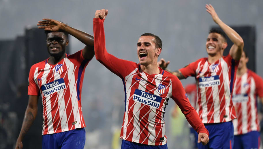 Atletico Madrid's French forward Antoine Griezmann (C) celebrates their victory past Atletico Madrid's Ghanaian midfielder Thomas (L) after winning the UEFA Europa League final football match between Olympique de Marseille and Club Atletico de Madrid at the Parc OL stadium in Decines-Charpieu, near Lyon on May 16, 2018. - Atletico won 3-0. (Photo by Philippe DESMAZES / AFP)        (Photo credit should read PHILIPPE DESMAZES/AFP/Getty Images)