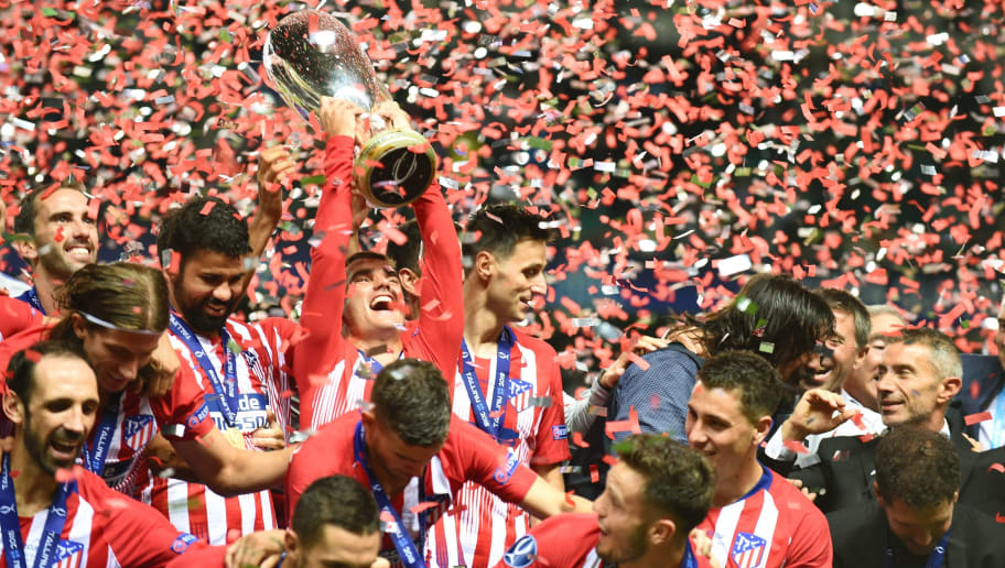 Atletico Madrid's French forward Antoine Griezmann holds up the trophy as he celebrates with teammates after winning the UEFA Super Cup football match Atletico de Madrid vs Real Madrid CF at the Lillekula Stadium in Tallinn, Estonia, on August 15, 2018. (Photo by Janek SKARZYNSKI / AFP)        (Photo credit should read JANEK SKARZYNSKI/AFP/Getty Images)