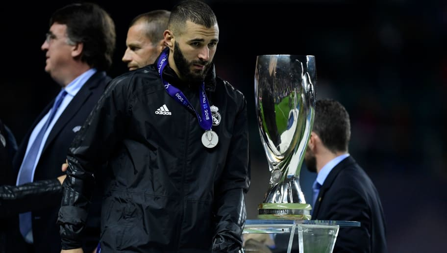 Real Madrid's French forward Karim Benzema walks past the trophy at the end of the UEFA Super Cup football match between Real Madrid and Atletico Madrid at the Lillekula Stadium in the Estonian capital Tallinn on August 15, 2018. (Photo by JAVIER SORIANO / AFP)        (Photo credit should read JAVIER SORIANO/AFP/Getty Images)