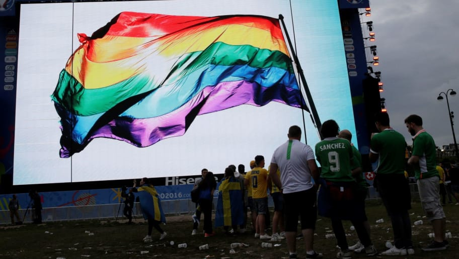 Supporters stand in front of a giant screen displaying a rainbow flag to pay tribute to the victims of the shooting of Orlando, in a fan zone in Paris during the Euro 2016 football tournament on June 13, 2016.  / AFP PHOTO / Thomas SAMSON        (Photo credit should read THOMAS SAMSON/AFP/Getty Images)