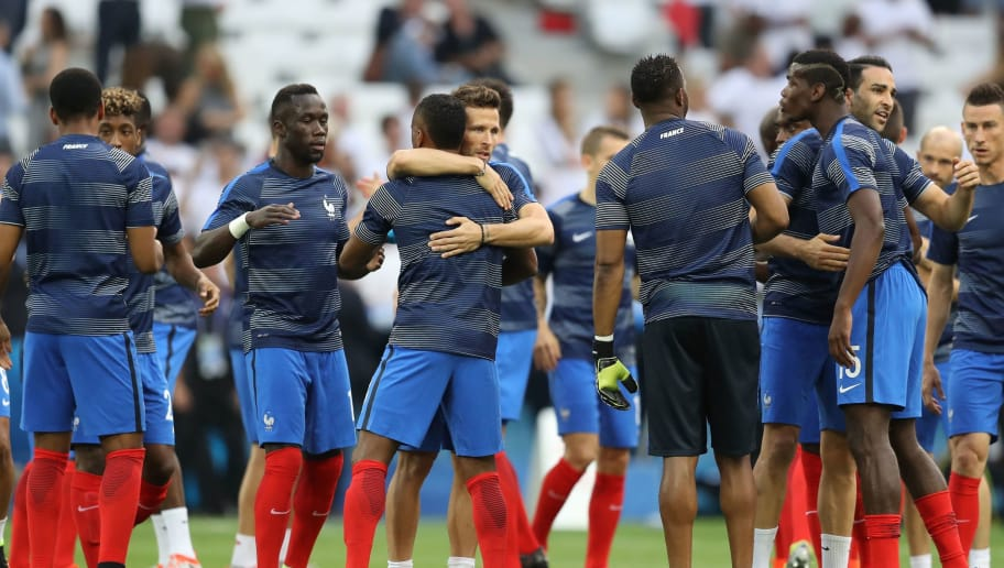 France's midfielder Yohan Cabaye (C) hugs France's defender Patrice Evra (4L) prior to the Euro 2016 semi-final football match between Germany and France at the Stade Velodrome in Marseille on July 7, 2016.  / AFP / Valery HACHE        (Photo credit should read VALERY HACHE/AFP/Getty Images)