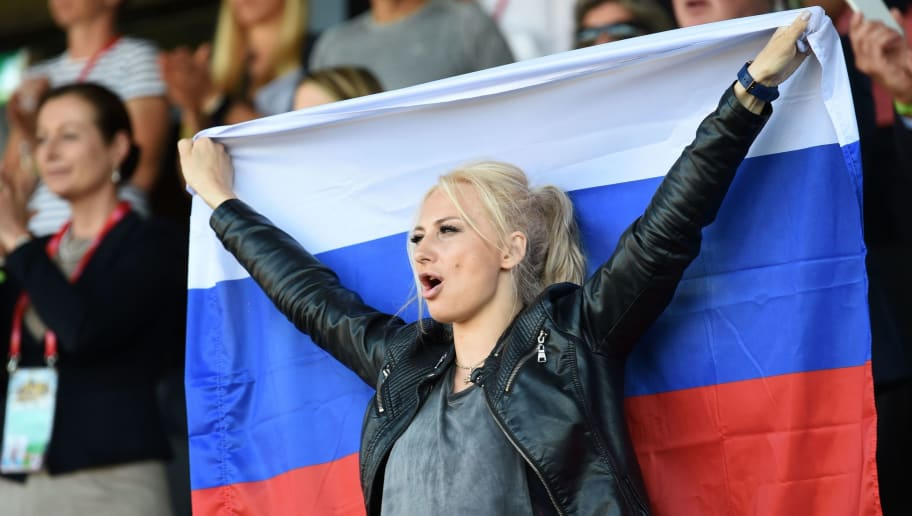 A Russia fan holding a flag cheers ahead of the UEFA Women's Euro 2017 football match between Sweden and Russia at Stadion De Adelaarshorst in Deventer on July 21, 2017. / AFP PHOTO / DANIEL MIHAILESCU        (Photo credit should read DANIEL MIHAILESCU/AFP/Getty Images)