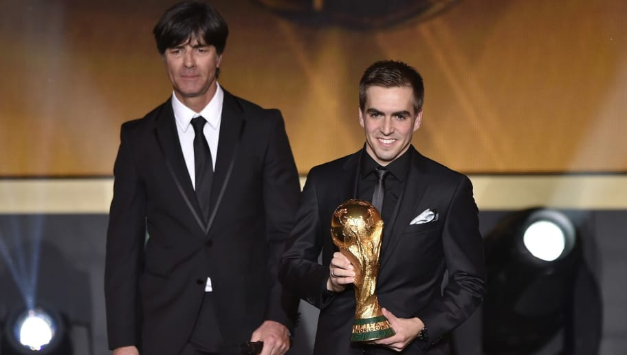 Bayern Munich and Germany defender Philipp Lahm (R) and Germany's coach Joachim Loew (L) stand on stage with the World Cup currently held by Germany during the 2014 FIFA Ballon d'Or award ceremony at the Kongresshaus in Zurich on January 12, 2015. AFP PHOTO / FABRICE COFFRINI        (Photo credit should read FABRICE COFFRINI/AFP/Getty Images)