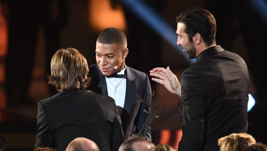 Paris Saint-Germain's French forward Kylian Mbappe (C) is congratulated by Real Madrid's Croatian midfielder Luka Modric (L) and Paris Saint-Germain's Italian goalkeeper Gianluigi Buffon after receiving the Koppa Trophy during the 2018 FIFA Ballon d'Or award ceremony at the Grand Palais in Paris on December 3, 2018. - The winner of the 2018 Ballon d'Or will be revealed at a glittering ceremony in Paris on December 3 evening, with Croatia's Luka Modric and a host of French World Cup winners all hoping to finally end the 10-year duopoly of Cristiano Ronaldo and Lionel Messi. (Photo by FRANCK FIFE / AFP)        (Photo credit should read FRANCK FIFE/AFP/Getty Images)