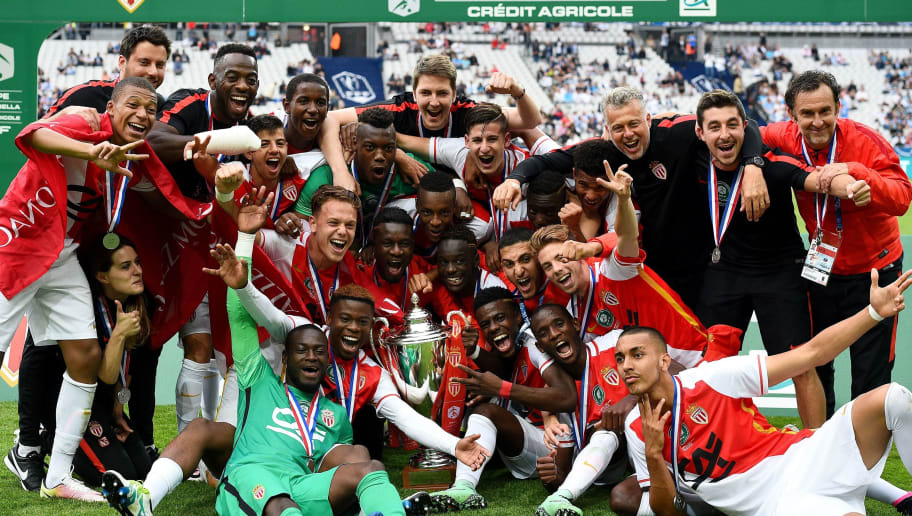 Monaco's players pose with the trophy as they celebrate after winning the French U19 Gambardella Cup final football match between Monaco and Lens on May 21, 2016 at the Stade de France in Saint-Denis, north of Paris.  / AFP / FRANCK FIFE        (Photo credit should read FRANCK FIFE/AFP/Getty Images)