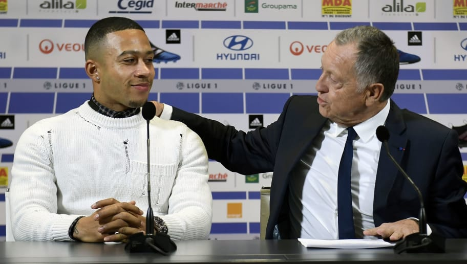 Lyon's football club new Dutch forward Memphis Depay (L) listens as Lyon's French president Jean-Michel Aulas speaks during a press conference on January 20, 2017 at the Parc Olympique Lyonnais in Lyon, eastern France.  / AFP / PHILIPPE DESMAZES        (Photo credit should read PHILIPPE DESMAZES/AFP/Getty Images)