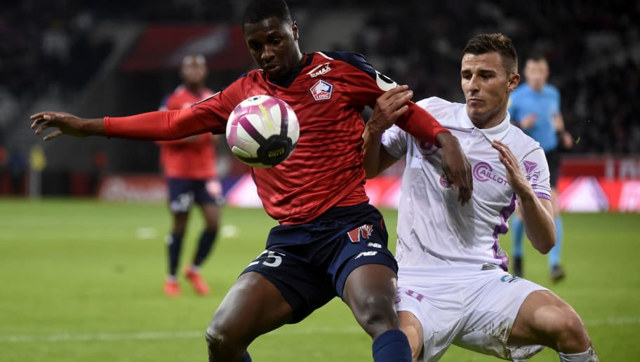 Lille's French defender Fode Ballo-Toure (L) vies with Reims' Remi Oudin during the French L1 football match between Lille and Reims on December 9, 2018 at the Pierre Mauroy Stadium in Villeneuve-d'Ascq. (Photo by FRANCOIS LO PRESTI / AFP)        (Photo credit should read FRANCOIS LO PRESTI/AFP/Getty Images)