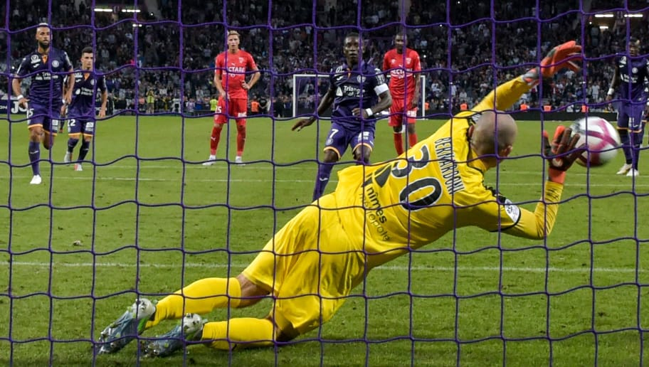 Nimes's French goalkeeper Paul Bernardoni(front C) jumps and stop a penalty kick of Toulouse's Ivorian forward Max-Alain Gradel (rear C) during the French L1 football match between Toulouse and Nimes, on August 25, 2018, at the Municipal Stadium, in Toulouse, southern France. (Photo by PASCAL PAVANI / AFP)        (Photo credit should read PASCAL PAVANI/AFP/Getty Images)