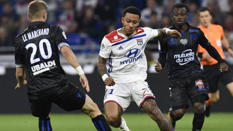 Lyon's Dutch forward Memphis Depay (C) vies with Nice's Ivorian midfielder Jean Michael Seri (R) and Nice's French defender Maxime Le Marchand (L) during the French L1 football match between Olympique Lyonnais and OGC Nice, on May 19, 2018, at the Groupama Stadium in Decines-Charpieu near Lyon, central-eastern France. (Photo by PHILIPPE DESMAZES / AFP)        (Photo credit should read PHILIPPE DESMAZES/AFP/Getty Images)