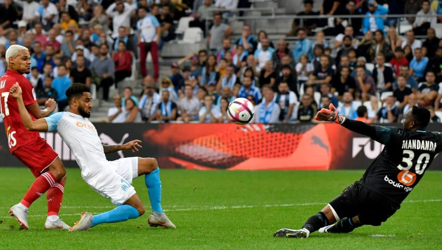 Strasbourg's French defender Kenny Lala (L) shoots and score a goal past Marseille's French defender Jordan Amavi (C) and Marseille's French goalkeeper Steve Mandanda (R) during the French L1 football match between Marseille (OM) and Strasbourg (RCSA) at the Velodrome stadium in Marseille on September 26, 2018. (Photo by GERARD JULIEN / AFP)        (Photo credit should read GERARD JULIEN/AFP/Getty Images)