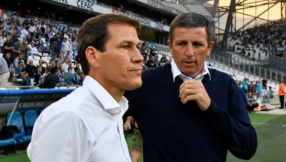 Marseille's French coach Rudi Garcia (L) speaks with Strasbourg's French coach Thierry Laurey (R)  during the French L1 football match between Marseille (OM) and Strasbourg (RCSA) at the Velodrome stadium in Marseille on September 26, 2018. (Photo by GERARD JULIEN / AFP)        (Photo credit should read GERARD JULIEN/AFP/Getty Images)
