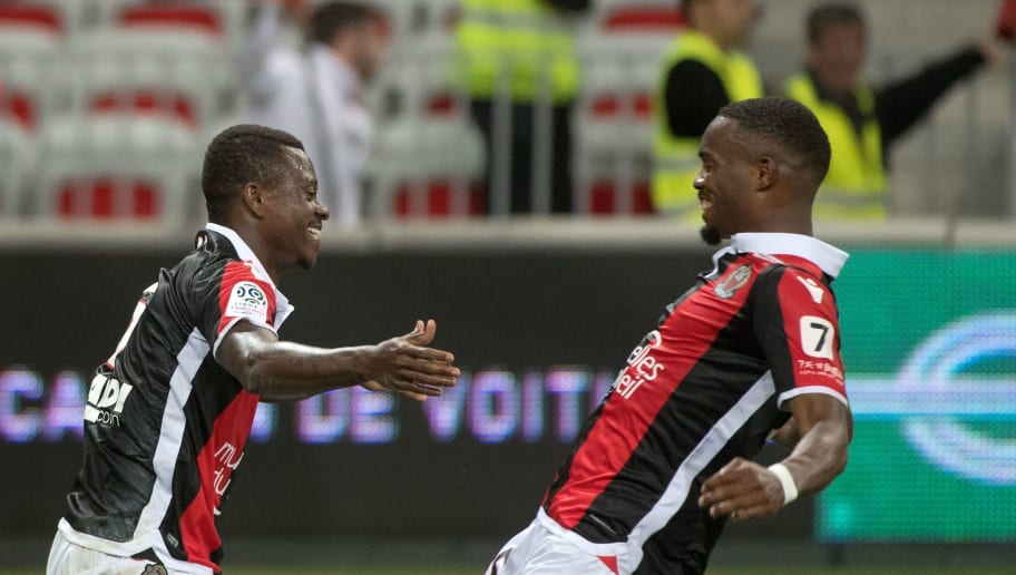Nice's Ivorian midfielder Jean Michael Seri (L) is congratulated by Nice's French midfielder Wylan Cyprien after scoring during the French L1 football match Nice vs Caen on May 12, 2018 at the Allianz Rivieira in Nice, southeastern France. (Photo by BERTRAND LANGLOIS / AFP)        (Photo credit should read BERTRAND LANGLOIS/AFP/Getty Images)