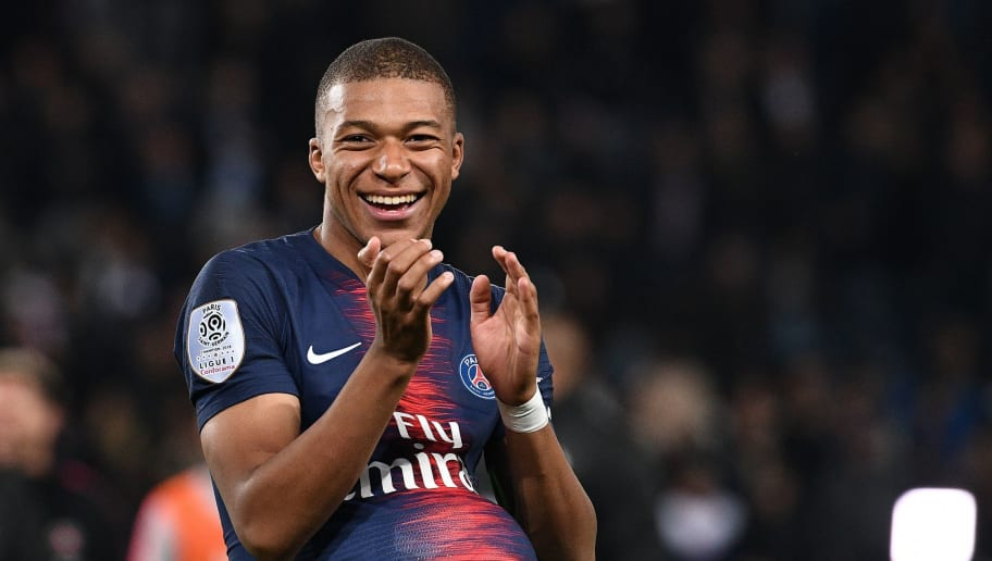 Paris Saint-Germain's French forward Kylian Mbappe celebrates as he hides the match's ball under his jersey after scoring four goals and win the French L1 football match between Paris Saint-Germain (PSG) and Olympique de Lyon (OL) on October 7, 2018 at the Parc des Princes stadium in Paris. (Photo by FRANCK FIFE / AFP)        (Photo credit should read FRANCK FIFE/AFP/Getty Images)