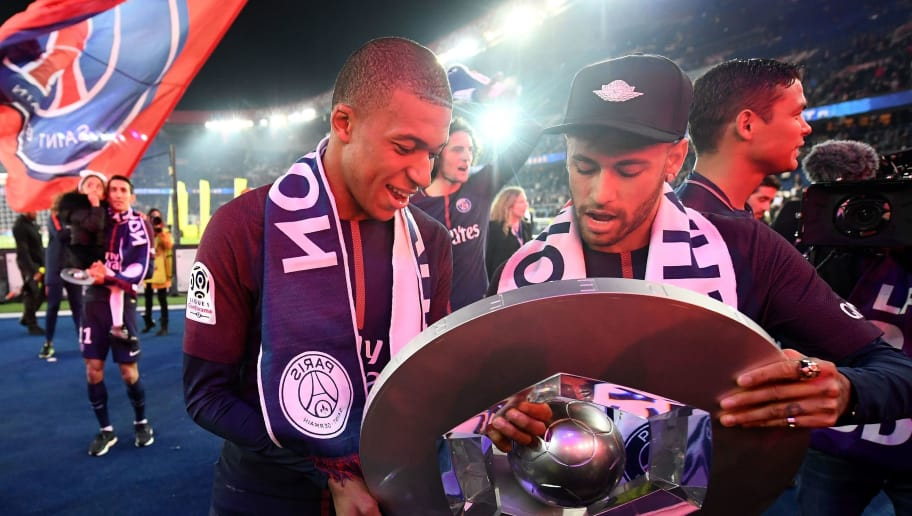 Paris Saint-Germain's French forward Kylian Mbappe (C) and teammate Brazilian forward Neymar look at a trophy as they celebrate with teammates after winning the French L1 title at the end of the French L1 football match Paris Saint-Germain (PSG) vs Rennes at The Parc des Princes Stadium in Paris on May 12, 2018. (Photo by FRANCK FIFE / AFP)        (Photo credit should read FRANCK FIFE/AFP/Getty Images)
