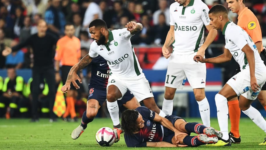 Paris Saint-Germain's Uruguayan forward Edinson Cavani (DOWN) reacts on the ground as Saint-Etienne's French midfielder Yann Mvila (L) controls the ball during the French L1 football match between Paris Saint-Germain (PSG) and Saint-Etienne (ASSE) at the Parc des Princes stadium in Paris on September 14, 2018. (Photo by Anne-Christine POUJOULAT / AFP)        (Photo credit should read ANNE-CHRISTINE POUJOULAT/AFP/Getty Images)
