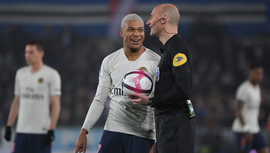 Paris Saint-Germain's French forward Kylian Mbappe (L) gestures as he speaks with French referee Antony Gautier (R) during the French L1 football match between Strasbourg and Paris Saint-Germain (PSG) at the Stade de la Meinau stadium, in Strasbourg, on December 5, 2018. (Photo by Patrick HERTZOG / AFP)        (Photo credit should read PATRICK HERTZOG/AFP/Getty Images)