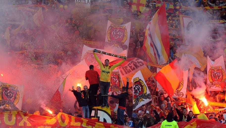 Lens' supporters light flares and cheer for their team during the French L2 football match between Lens and Brest at Felix Bollaert stadium in Lens on May 9, 2014. AFP PHOTO/DENIS CHARLET        (Photo credit should read DENIS CHARLET/AFP/Getty Images)