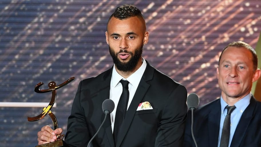 Lens' forward John Bostock (L) receives the Best Ligue 2 player award from French former player Jean Pierre Papin (C) next to Best Ligue 2 goalkeeper Nicolas Douchez, during the 26th edition of the UNFP (French National Professional Football players' Union) trophies ceremony at the Pavillon d'Armenonville in Paris, on May 15, 2017.  / AFP PHOTO / FRANCK FIFE        (Photo credit should read FRANCK FIFE/AFP/Getty Images)