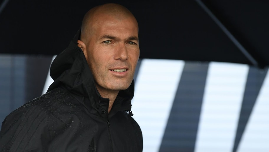 Former French football player and former Real Madrid coach Zinedine Zidane looks on as he shelters under an umbrella in Saint Denis, suburban Paris on June 11, 2018 during an event marking the 20th anniversary of France's 1998 World Cup victory. (Photo by Eric FEFERBERG / AFP)        (Photo credit should read ERIC FEFERBERG/AFP/Getty Images)
