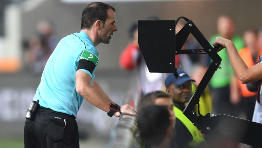 Referee Marco Fritz checks the Video assistant referee (VAR) during the German first division Bundesliga football match between FC Augsburg and Borussia Dortmund in Augsburg, southern Germany on September 30, 2017. / AFP PHOTO / Christof STACHE / RESTRICTIONS: DURING MATCH TIME: DFL RULES TO LIMIT THE ONLINE USAGE TO 15 PICTURES PER MATCH AND FORBID IMAGE SEQUENCES TO SIMULATE VIDEO. == RESTRICTED TO EDITORIAL USE == FOR FURTHER QUERIES PLEASE CONTACT DFL DIRECTLY AT + 49 69 650050  / The erroneous mention[s] appearing in the metadata of this photo by Christof STACHE has been modified in AFP systems in the following manner: [Referee Marco Fritz checks the Video assistant referee (VAR) during the German first division Bundesliga football match between FC Augsburg and Borussia Dortmund in Augsburg, southern Germany on September 30, 2017.] instead of [Referee Marco Fritz checks the Video assistant referee (VAR) after blowing for a penalty during the German first division Bundesliga football match between Borussia Moenchengladbach and Hannover 96 in Moenchengladbach, western Germany on September 30, 2017.]. Please immediately remove the erroneous mention[s] from all your online services and delete it (them) from your servers. If you have been authorized by AFP to distribute it (them) to third parties, please ensure that the same actions are carried out by them. Failure to promptly comply with these instructions will entail liability on your part for any continued or post notification usage. Therefore we thank you very much for all your attention and prompt action. We are sorry for the inconvenience this notification may cause and remain at your disposal for any further information you may require.        (Photo credit should read CHRISTOF STACHE/AFP/Getty Images)