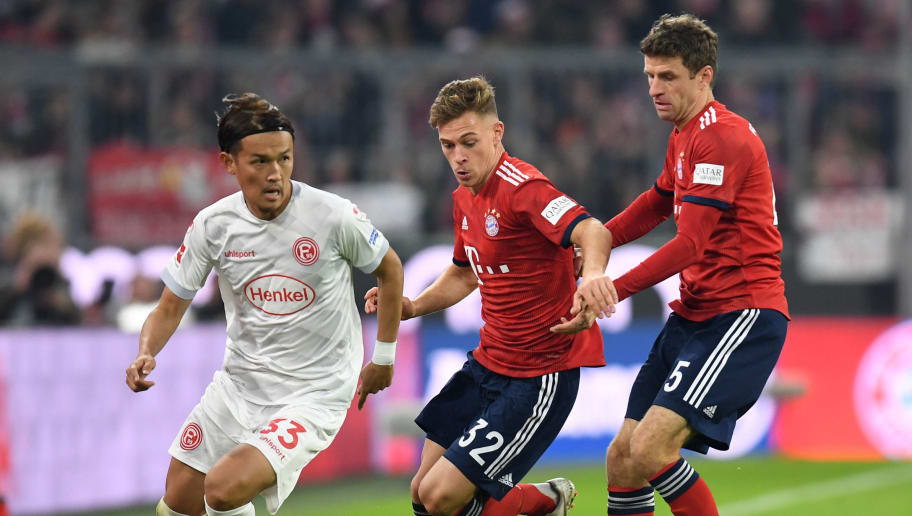 Fortuna Duesseldorf's Japanese midfielder Takashi Usami (L) vies for the ball with Bayern Munich's German midfielder Joshua Kimmich (C) and Bayern Munich's German forward Thomas Mueller (R) during the German first division Bundesliga football match between FC Bayern Munich and Fortuna Duesseldorf in Munich, southern Germany on November 24, 2018. (Photo by Christof STACHE / AFP) / RESTRICTIONS: DFL REGULATIONS PROHIBIT ANY USE OF PHOTOGRAPHS AS IMAGE SEQUENCES AND/OR QUASI-VIDEO        (Photo credit should read CHRISTOF STACHE/AFP/Getty Images)