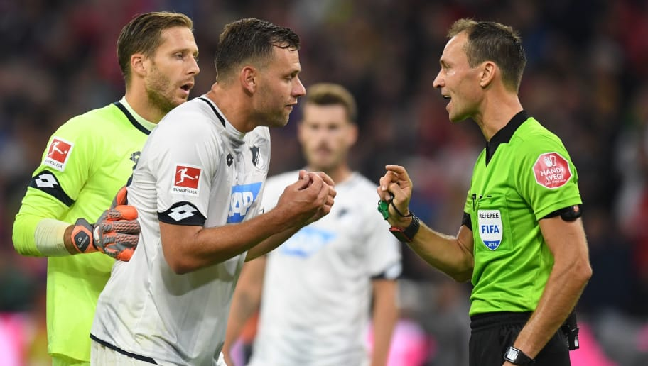 Hoffenheim's Hungarian forward Adam Szalai argues with referee Bastian Dankert during the German first division Bundesliga football match FC Bayern Munich v TSG 1899 Hoffenheim at the Allianz Arena in Munich, southern Germany on August 24, 2018. (Photo by Christof STACHE / AFP) / RESTRICTIONS: DFL REGULATIONS PROHIBIT ANY USE OF PHOTOGRAPHS AS IMAGE SEQUENCES AND/OR QUASI-VIDEO        (Photo credit should read CHRISTOF STACHE/AFP/Getty Images)