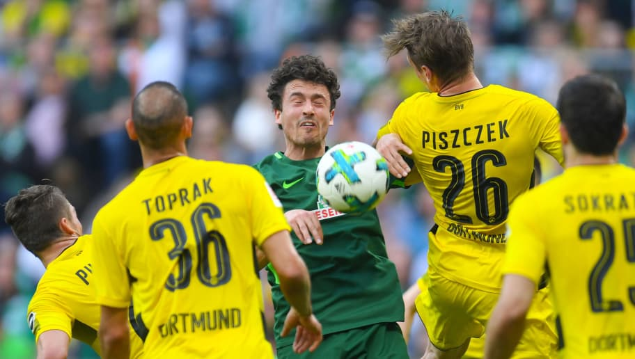 Dortmund's Turkish defender Omer Toprak, Dortmund's Polish defender Lukasz Piszczek and Bremen's Danish midfielder Thomas Delaney vie for the ball  during the German first division Bundesliga football match of Werder Bremen versus Borussia Dortmund on April 29, 2018 in Bremen. (Photo by Patrik STOLLARZ / AFP) / RESTRICTIONS: DURING MATCH TIME: DFL RULES TO LIMIT THE ONLINE USAGE TO 15 PICTURES PER MATCH AND FORBID IMAGE SEQUENCES TO SIMULATE VIDEO. == RESTRICTED TO EDITORIAL USE == FOR FURTHER QUERIES PLEASE CONTACT DFL DIRECTLY AT + 49 69 650050        (Photo credit should read PATRIK STOLLARZ/AFP/Getty Images)