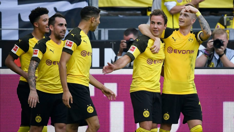 (L-R) Dortmund's English midfielder Jadon Sancho, Dortmund's Spanish forward Paco Alcacer, Dortmund's Moroccan defender Achraf Hakimi, Dortmund's German midfielder Mario Goetze and Dortmund's German forward Marco Reus celebrate the 3-2 against Augsburg during the German first division Bundesliga football match Borussia Dortmund vs FC Augsburg in Dortmund, western Germany, on October 6, 2018. (Photo by INA FASSBENDER / AFP) / RESTRICTIONS: DFL REGULATIONS PROHIBIT ANY USE OF PHOTOGRAPHS AS IMAGE SEQUENCES AND/OR QUASI-VIDEO        (Photo credit should read INA FASSBENDER/AFP/Getty Images)
