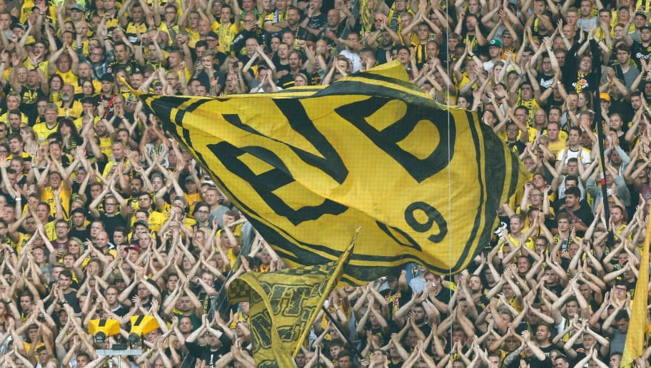 Fans of Borussia Dortmund cheer their team during the German First division Bundesliga football match between Borussia Dortmund and Hertha Berlin in Dortmund, western Germany, on August 26, 2017. / AFP PHOTO / INA FASSBENDER / RESTRICTIONS: DURING MATCH TIME: DFL RULES TO LIMIT THE ONLINE USAGE TO 15 PICTURES PER MATCH AND FORBID IMAGE SEQUENCES TO SIMULATE VIDEO. == RESTRICTED TO EDITORIAL USE == FOR FURTHER QUERIES PLEASE CONTACT DFL DIRECTLY AT + 49 69 650050        (Photo credit should read INA FASSBENDER/AFP/Getty Images)
