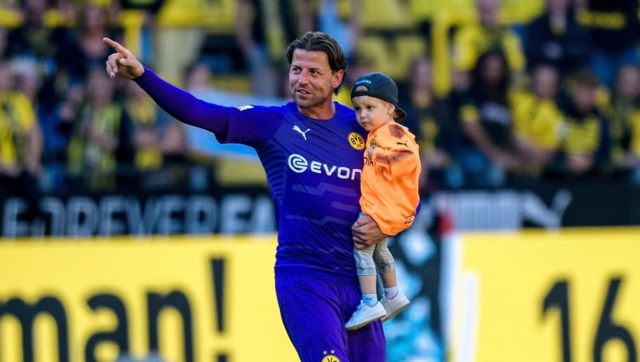 Dortmund's goalkeeper Roman Weidenfeller holds a child as he bids farewell to supporters after the German first division Bundesliga football match Borussia Dortmund vs Mainz 05 in Dortmund, western Germany, on May 5, 2018. (Photo by SASCHA SCHUERMANN / AFP) / RESTRICTIONS: DURING MATCH TIME: DFL RULES TO LIMIT THE ONLINE USAGE TO 15 PICTURES PER MATCH AND FORBID IMAGE SEQUENCES TO SIMULATE VIDEO. == RESTRICTED TO EDITORIAL USE == FOR FURTHER QUERIES PLEASE CONTACT DFL DIRECTLY AT + 49 69 650050        (Photo credit should read SASCHA SCHUERMANN/AFP/Getty Images)