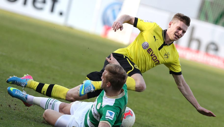 Dortmund's Polish defender Lukasz Piszczek (R) falls next to Fuerth's midfielder Johannes Geis as they vie for the ball during the German first division Bundesliga football match SpVgg Greuther Fuerth vs Borussia Dortmund in Fuerth, southwestern Germany, on April 13, 2013. Dortmund won 6-1. AFP PHOTO / DANIEL ROLAND  DFL RULES TO LIMIT THE ONLINE USAGE DURING MATCH TIME TO 15 PICTURES PER MATCH. IMAGE SEQUENCES TO SIMULATE VIDEO IS NOT ALLOWED AT ANY TIME. FOR FURTHER QUERIES PLEASE CONTACT DFL DIRECTLY AT + 49 69 650050.        (Photo credit should read DANIEL ROLAND/AFP/Getty Images)