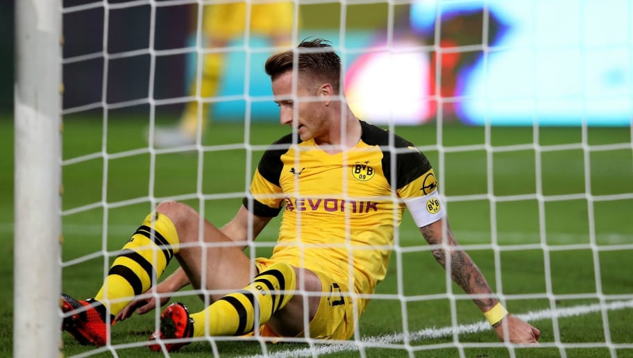 Dortmund's German forward Marco Reus sits on the pitch during the German first division Bundesliga football match Hannover 96 vs Borussia Dortmund in Hanover, northern Germany, on August 31, 2018. (Photo by Ronny Hartmann / AFP) / RESTRICTIONS: DFL REGULATIONS PROHIBIT ANY USE OF PHOTOGRAPHS AS IMAGE SEQUENCES AND/OR QUASI-VIDEO        (Photo credit should read RONNY HARTMANN/AFP/Getty Images)