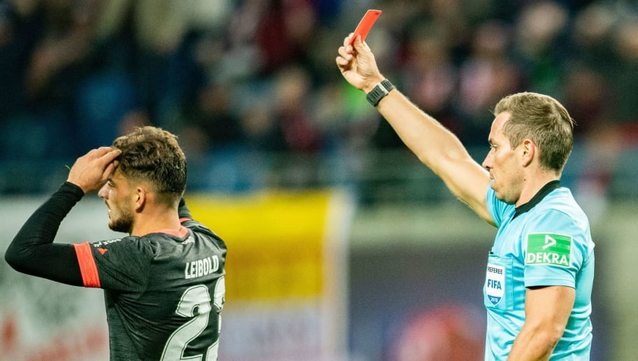Referee Tobias Stieler shows the red card to Nuernberg's German defender Tim Leibold during the German first division Bundesliga football match RB Leipzig vs FC Nuremberg in Leipzig, eastern Germany, on October 7, 2018. (Photo by ROBERT MICHAEL / AFP) / RESTRICTIONS: DFL REGULATIONS PROHIBIT ANY USE OF PHOTOGRAPHS AS IMAGE SEQUENCES AND/OR QUASI-VIDEO        (Photo credit should read ROBERT MICHAEL/AFP/Getty Images)