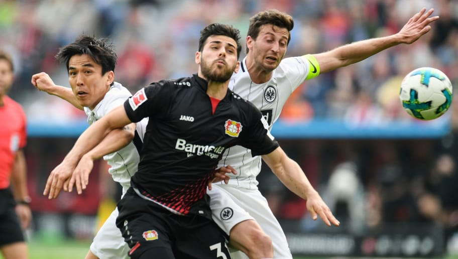 Leverkusen's German forward Kevin Volland (C), Frankfurt's Japanese midfielder Makoto Hasebe (L) and Frankfurt's Argentinian defender David Abraham vie for the ball during the German first division Bundesliga football match Bayer 04 Leverkusen vs Eintracht Frankfurt, in Leverkusen, western Germany, on April 14, 2018. / AFP PHOTO / Patrik STOLLARZ / RESTRICTIONS: DURING MATCH TIME: DFL RULES TO LIMIT THE ONLINE USAGE TO 15 PICTURES PER MATCH AND FORBID IMAGE SEQUENCES TO SIMULATE VIDEO. == RESTRICTED TO EDITORIAL USE == FOR FURTHER QUERIES PLEASE CONTACT DFL DIRECTLY AT + 49 69 650050         (Photo credit should read PATRIK STOLLARZ/AFP/Getty Images)