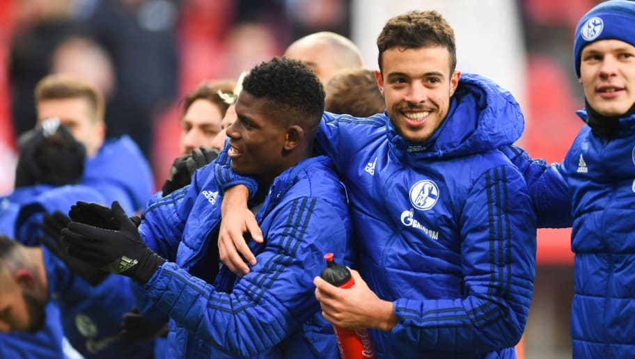 Schalke's Swiss forward Breel Embolo (L) and Schalke's Argentinian forward Franco di Santo joke as team players celebrate winning their German first division Bundesliga football match Bayer 04 Leverkusen vs FC Schalke 04, in Leverkusen, western Germany, on February 25, 2018. / AFP PHOTO / Patrik STOLLARZ / RESTRICTIONS: DURING MATCH TIME: DFL RULES TO LIMIT THE ONLINE USAGE TO 15 PICTURES PER MATCH AND FORBID IMAGE SEQUENCES TO SIMULATE VIDEO. == RESTRICTED TO EDITORIAL USE == FOR FURTHER QUERIES PLEASE CONTACT DFL DIRECTLY AT + 49 69 650050         (Photo credit should read PATRIK STOLLARZ/AFP/Getty Images)