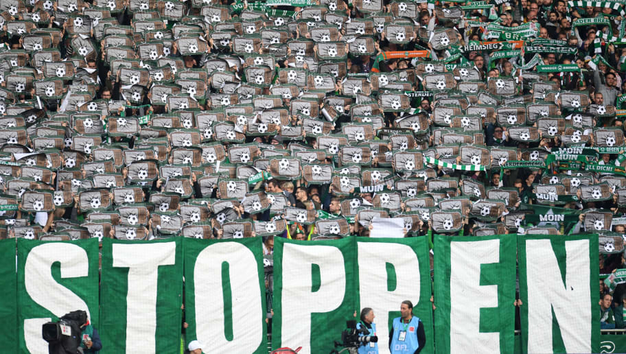Bremen supporters hold flyers in protest prior to the German first division Bundesliga football match Werder Bremen v Hertha Berlin in Bremen, northern Germany on September 25, 2018. (Photo by Patrik STOLLARZ / AFP) / RESTRICTIONS: DFL REGULATIONS PROHIBIT ANY USE OF PHOTOGRAPHS AS IMAGE SEQUENCES AND/OR QUASI-VIDEO        (Photo credit should read PATRIK STOLLARZ/AFP/Getty Images)