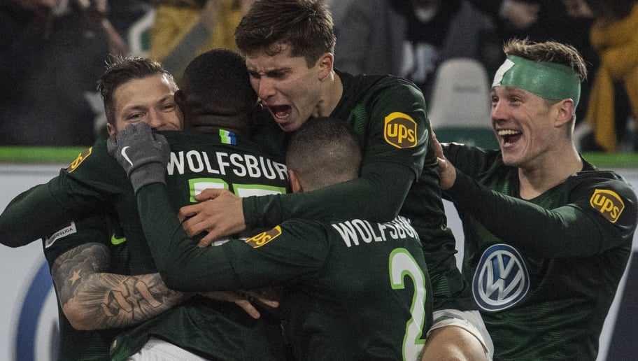 Wolfsburg players celebrate after Wolfsburg's French defender Jerome Roussillon (2nd from L) scored during the German first division Bundesliga football match between VfL Wolfsburg and RB Leipzig in Wolfsburg, northern Germany on November 24, 2018. (Photo by John MACDOUGALL / AFP) / RESTRICTIONS: DFL REGULATIONS PROHIBIT ANY USE OF PHOTOGRAPHS AS IMAGE SEQUENCES AND/OR QUASI-VIDEO        (Photo credit should read JOHN MACDOUGALL/AFP/Getty Images)