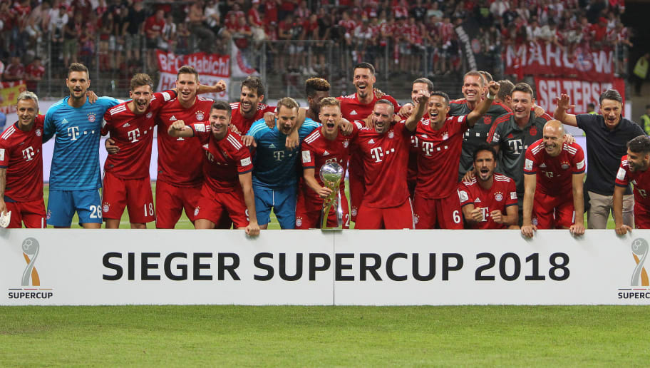 Bayern Munich players pose for a picture with the trophy after winning the German Supercup football match between Eintracht Frankfurt and Bayern Munich in Frankfurt am Main, western Germany, on August 12, 2018. (Photo by Daniel ROLAND / AFP) / RESTRICTIONS: ACCORDING TO DFB RULES IMAGE SEQUENCES TO SIMULATE VIDEO IS NOT ALLOWED DURING MATCH TIME. MOBILE (MMS) USE IS NOT ALLOWED DURING AND FOR FURTHER TWO HOURS AFTER THE MATCH. == RESTRICTED TO EDITORIAL USE == FOR MORE INFORMATION CONTACT DFB DIRECTLY AT +49 69 67880 /         (Photo credit should read DANIEL ROLAND/AFP/Getty Images)