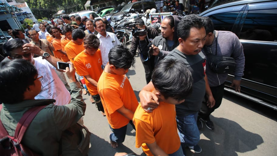 Indonesian policemen escort eights suspects of supporters of Bandung football following a violence beating to a Persija supporter one day earlier, in Bandung on September 24, 2018. - More than a dozen people have been arrested after an Indonesian football fan was clubbed to death with iron bars and wood planks by supporters of a rival team, police said on September 24. The deadly incident happened on September 23 before a match between host club Bandung and Persija Jakarta, bitter rivals in Indonesia's top flight professional league. (Photo by STR / AFP)        (Photo credit should read STR/AFP/Getty Images)