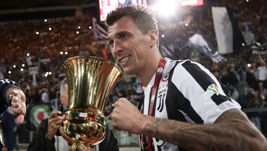 Juventus' forward from Croatia Mario Mandzukic celebrates with the trophy at the end of the Italian Tim Cup (Coppa Italia) final Juventus vs AC Milan at the Olympic stadium on May 9, 2018 in Rome. - Juventus crushed AC Milan 4-0 on today at the Stadio Olimpico to win a fourth consecutive Italian Cup. Mehdi Benatia opened the floodgates after 56 minutes for the first of a double of the night for the Moroccan with Douglas Costa also finding the net in the space of nine minutes. A Nikola Kalinic own goal accounted for the fourth (Photo by Isabella Bonotto / AFP)        (Photo credit should read ISABELLA BONOTTO/AFP/Getty Images)