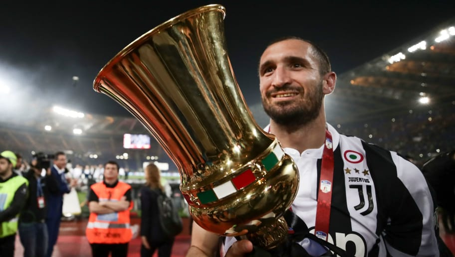 Juventus' defender from Italy Giorgio Chiellini celebrates with the trophy at the end of the Italian Tim Cup (Coppa Italia) final Juventus vs AC Milan at the Olympic stadium on May 9, 2018 in Rome. - Juventus crushed AC Milan 4-0 on today at the Stadio Olimpico to win a fourth consecutive Italian Cup. Mehdi Benatia opened the floodgates after 56 minutes for the first of a double of the night for the Moroccan with Douglas Costa also finding the net in the space of nine minutes. A Nikola Kalinic own goal accounted for the fourth (Photo by Isabella Bonotto / AFP)        (Photo credit should read ISABELLA BONOTTO/AFP/Getty Images)