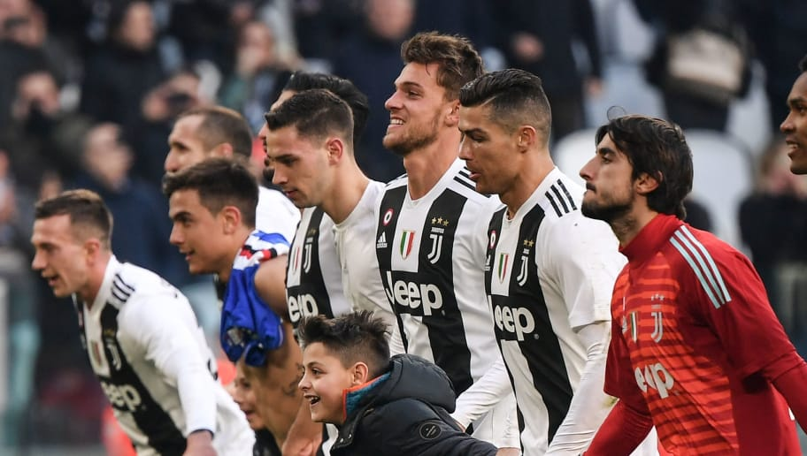 A boy who took to the pitch after the game celebrates with Juventus' Portuguese forward Cristiano Ronaldo (2ndR) and teammates after Ronaldo invited him to join them at the end of the Italian Serie A football match Juventus vs Sampdoria on December 29, 2018 at the Juventus stadium in Turin. (Photo by Marco BERTORELLO / AFP)        (Photo credit should read MARCO BERTORELLO/AFP/Getty Images)