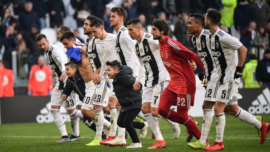 Two boys who took to the pitch after the game celebrate with Juventus' Portuguese forward Cristiano Ronaldo (C-R) and teammates at the end of the Italian Serie A football match Juventus vs Sampdoria on December 29, 2018 at the Juventus stadium in Turin. (Photo by Marco BERTORELLO / AFP)        (Photo credit should read MARCO BERTORELLO/AFP/Getty Images)