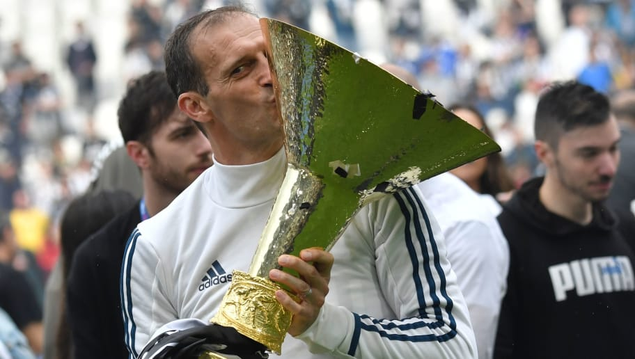 Juventus' coach from Italy Massimiliano Allegri kisses the trophy during the victory ceremony following the Italian Serie A last football match of the season Juventus versus Verona, on May 19, 2018 at the Allianz Stadium in Turin. Juventus won their 34th Serie A title (scudetto) and seventh in succession. (Photo by Andreas SOLARO / AFP)        (Photo credit should read ANDREAS SOLARO/AFP/Getty Images)