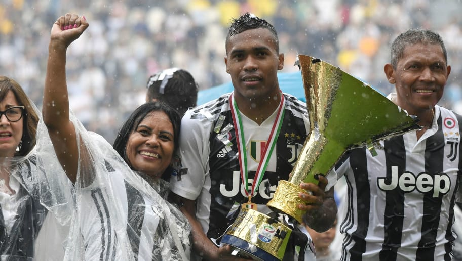 Juventus' defender from Brazil Alex Sandro poses with the trophy during the victory ceremony following the Italian Serie A last football match of the season Juventus versus Verona, on May 19, 2018 at the Allianz Stadium in Turin. Juventus won their 34th Serie A title (scudetto) and seventh in succession. (Photo by Marco BERTORELLO / AFP)        (Photo credit should read MARCO BERTORELLO/AFP/Getty Images)