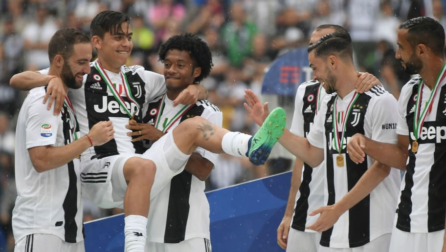 Juventus' forward from Argentina Gonzalo Higuain (L) jokes with teammates, Juventus' forward from Argentina Paulo Dybala (2ndL) and Juventus' forward from Colombia Juan Cuadrado (3rdL) during the trophy ceremony following the Italian Serie A last football match of the season Juventus versus Verona, on May 19, 2018 at the Allianz Stadium in Turin. Juventus won their 34th Serie A title (scudetto) and seventh in succession. (Photo by Marco BERTORELLO / AFP)        (Photo credit should read MARCO BERTORELLO/AFP/Getty Images)